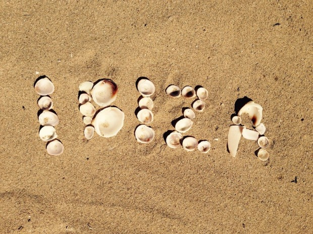Ibiza spelled with sea shells on the sand.
